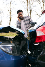 Young Male Driver Calling Car Insurance Company On Mobile Phone After Road Traffic Accident