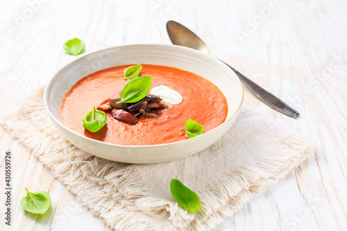 Homemade tomato soup with grilled eggplant, cream and basil