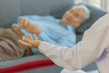 Doctor Wearing White Lab Coat Open His Left Hand Up When Explaining To Old Fat Asian Male Patient Wearing Light Blue Shirt Laying Down Holding His Hand Together On Gray Sofa In Blurred Background
