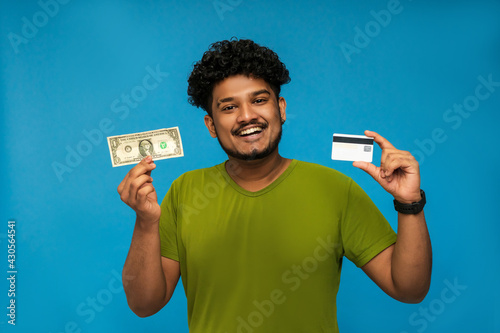 Papel de parede Against a blue background, a smiling Indian holding a dollar and a bank card in