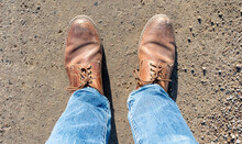 Blue Jeans And Old Brown Shoes With Scuff Marks And Tied, Brown Shoe Laces Firmly Placed On A Dirt Road.