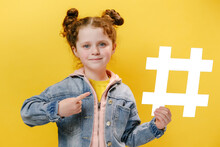 Portrait Of Nice Adorable Happy Cute Little Girl Kid In Denim Jacket Pointing To Big White Hashtag Symbol And Smiling At Camera, Child Blogger Showing Hash Sign, Isolated On Yellow Studio Background