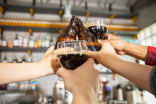 Close Up Hands Clinking Glasses And Bottles With Beer. Emotional Fans Cheering For Favourite Team, Watching On Exciting Game. Concept Of Friendship, Leisure Activity, Emotions