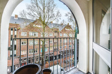 Arched Window Of Modern Apartment With Balcony Fence Viewing Spring Tree And Brick House