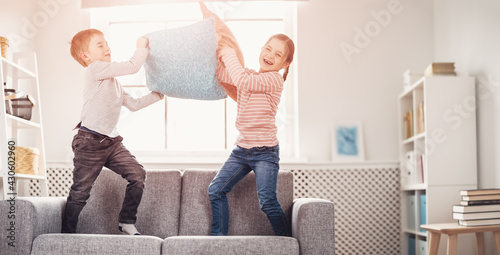 Valokuva Cute children fighting by pillows on the sofa