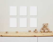 6 Blank Vertical Frames Mockup On Wall For Nursery Wall Art Display, Baby Room Six White Frames Mock Up, Wooden Shelf, Soft Toys And Wooden Toys On Shelf.