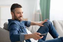 Relaxed Bearded Man Switching Channels On TV