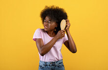 Annoyed African American Woman Having Problem Brushing Her Bushy Curly Hair On Yellow Studio Background