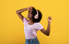 Carefree African American Woman In Wireless Headphones Dancing And Enjoying Music With Closed Eyes, Yellow Background