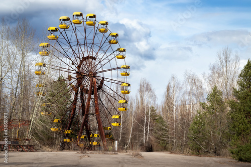 Fotografie, Obraz Old abandoned rusty metal radioactive yellow ferris wheel against dramatic sky i