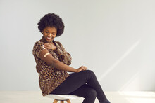 Happy Young African Woman Shows Arm After Getting Covid-19 Vaccine Jab. Smiling Woman Promoting Safe Coronavirus (Covid19) Vaccination Sitting On Chair On Studio Background With Free Text Copyspace