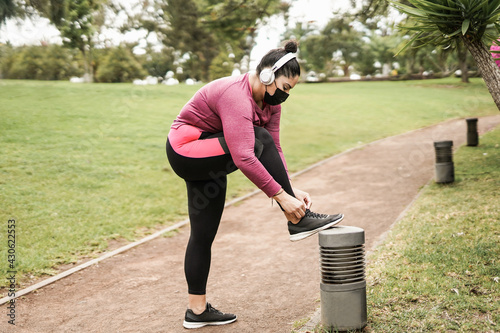 Tablou Canvas Young curvy woman doing sport outdoor in the city park while wearing safety face