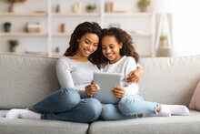 Cute African Mother And Daughter Reading Books On Digital Tablet
