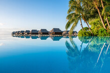 Infinity Pool And Overwater Bungalows At A Luxury Beach Resort