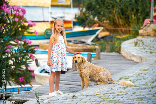 Canvas Print A little girl with a dog on the embankment by the river in a white sundress in the city of Dalyan
