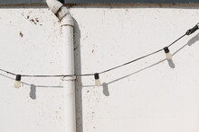 Old String Or Rope Lights Hung Across A Grungy Wall With A Drain Pipe - Specular Or Stark Light