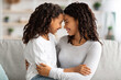 Cute black mother and daughter cuddling at home