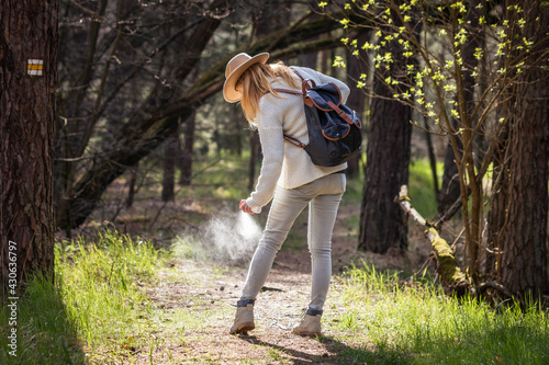 Woman spraying insect repellent against tick at her legs Fotobehang