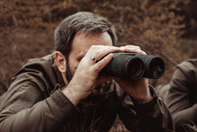 A Hunter In Camouflage Looks Through Binoculars, A Man Looks Out For Game Through Binoculars, Soft Focus, Brown Tint, There Is A Slight Noise