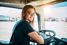 Portrait Of Beautiful Young Woman Professional Truck Driver Sitting And Driving Big Truck. Inside Of Vehicle. People And Transportation Concept.