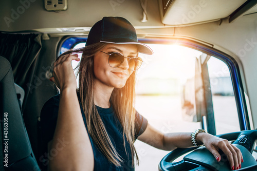 Portrait of beautiful young woman professional truck driver sitting and driving big truck. Inside of vehicle. People and transportation concept. - fototapety na wymiar
