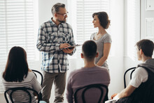 Pretty Mother Stands Next To Handsome Therapist Talking To Her Teenage Child During Group Meeting