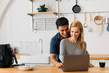 Romantic Young Caucasian Husband And Wife Using Laptop While Preparing Healthy Snacks In Air Fryer And Drinking Tea At Home
