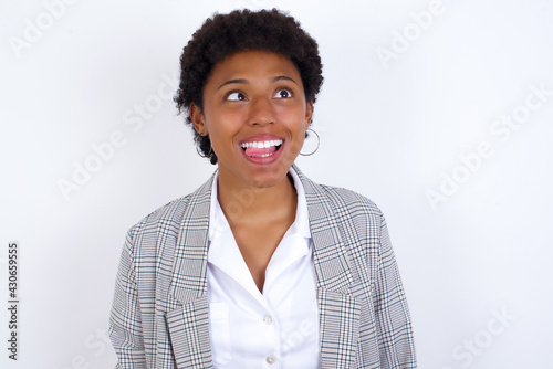 Платно African American businesswoman with curly bushy hair wears  formal clothes over white background showing grimace face crossing eyes and showing tongue