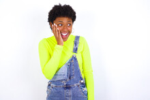 Young African American Woman With Short Hair Wearing Denim Overall Against White Wall Excited Looking To The Side Hand On Face. Advertisement And Amazement Concept.