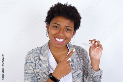 African American businesswoman with curly bushy hair wears  formal clothes over white background holding an invisible aligner and pointing at it. Dental healthcare and confidence concept. - fototapety na wymiar