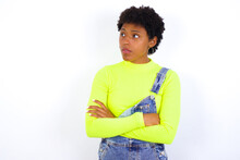 Serious African American Female With Curly Bushy Wears Jeans Overalls Over White Wall Keeps Hands Crossed Stands In Thoughtful Pose Concentrated Somewhere