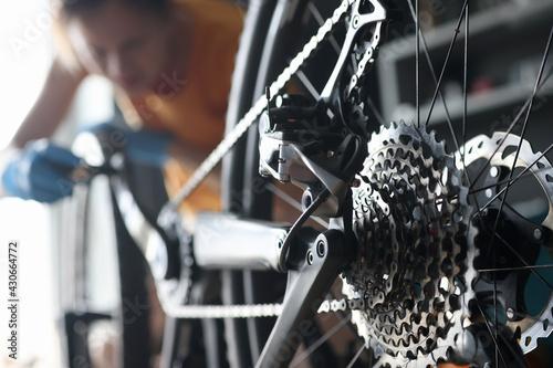 Fototapeta Master repairman repairing bicycle in workshop closeup obraz