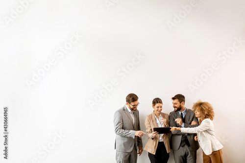 Fotografia Multiethnic business people using digital tablet while standing by the wall in t