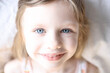 Portrait of little smiling girl with blue eyes