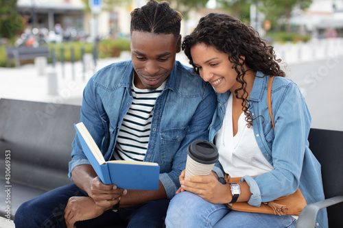 handsome loving couple reading sitiing on a bench - fototapety na wymiar