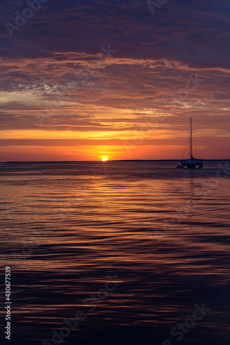 Boat on the ocean at sunset. Sailboats with sails. Sea yacht sailing along water.