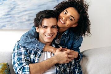 Portrait joyful happy mixed race couple, pretty african american curly girl tenderly hugging her hispanic boyfriend sitting on sofa, wearing casual clothes in living room, looking at camera, smiling