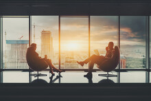 Two Business Partners Sitting In Front Of Each Other On Elegant Armchairs: A Businessman With A Laptop And A Woman Entrepreneur With A Paper Cup Of Coffee; Stunning Sunset Cityscape Outside The Window
