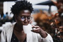 Portrait Of A Young Glamorous Black Female In Classy Spectacles Drinking A Hot Tea In A Street Cafe; Ravishing African Woman In Glasses Drinking A Delicious Latte From The Cup In An Outdoor Restaurant