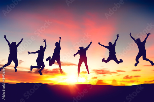 Silhouette happy friends jump on sunset sky at top of mountain abstract background. - fototapety na wymiar