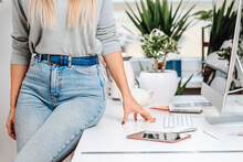 Elegant Woman Poses Sitting On A Table There Are Some Office Devices