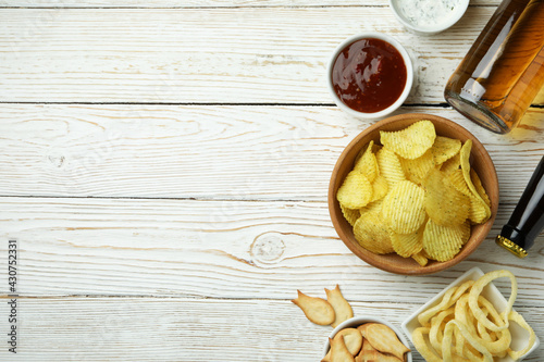 Fotografering Different snacks, beer and sauces on white wooden background