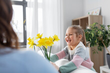 People, Family And Holidays Concept - Happy Little Daughter Giving Daffodil Flowers To Mother At Home
