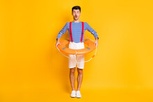 Full Length Photo Of Amazed Brunette Man Hold Lifeguard Circle Wear Summer Sailor Outfit Isolated On Yellow Color Background