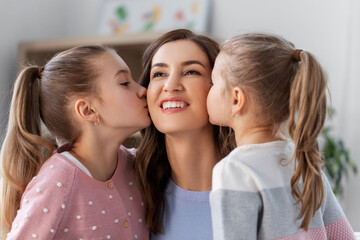 people, family and love concept - two daughters kissing happy mother at home