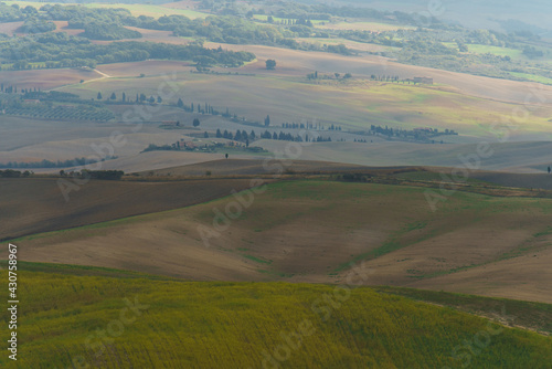 Fototapeta premium Autumn sunrise in Tuscany with wavy landscapes, fields, cypresses and clouds. Italy