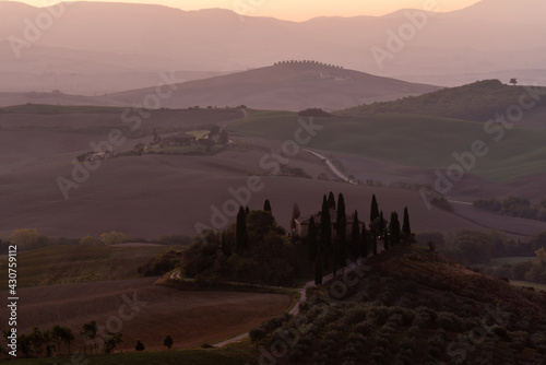 Fototapeta premium A view of a beautiful hilly Tuscan field in the golden morning light with a cypress farmhouse and hay bales in Italy. Val d'Orcia