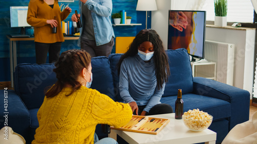 Fotografering African woman competing with friends playing backgammon wearing face mask keeping social distancing during social pandemic with covid19 drinking beer in living room