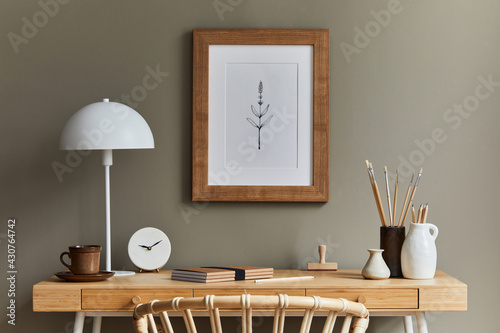 Fototapeta Stylish bohemian interior of home office space with wooden desk, rattan armchair, brown mock up poster frame, macrame, office supplies, lamp, decoration and elegant personal accessories in home decor. obraz