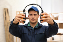 Worker Holding Safety Headphones Indoors, Focus On Hands. Hearing Protection Device